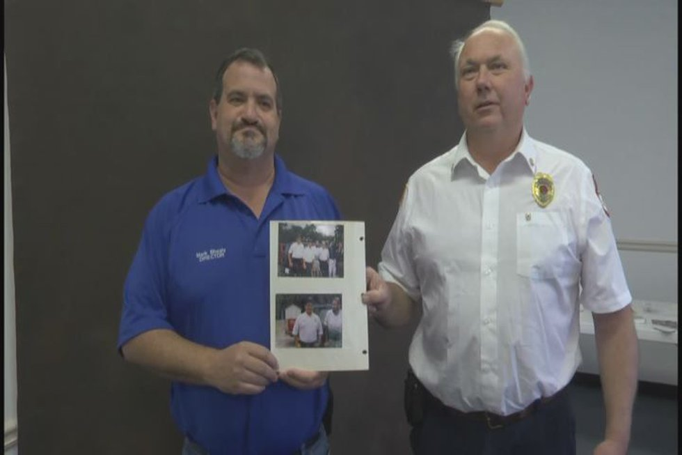 Shealy (left) and Conger (right) holding photos of Townsend's one year anniversary visit