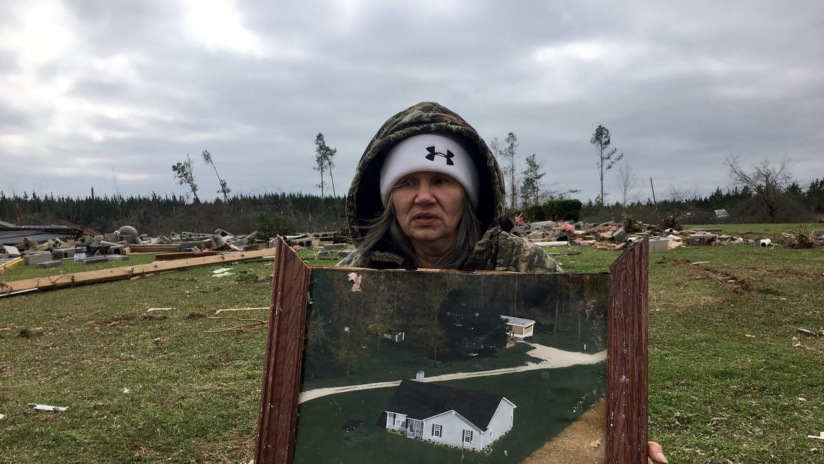 Julie Morrison holds a painting of her Lee County home that was destroyed in yesterday's...