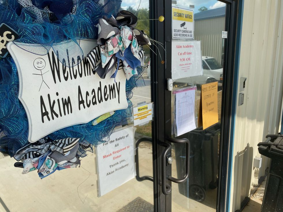 Akim Academy with the Letter of Revocation on the door.