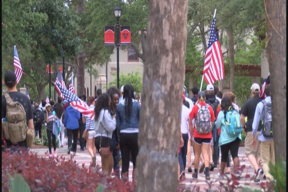 Students marched through campus Monday afternoon carrying flags, attempting to show their...