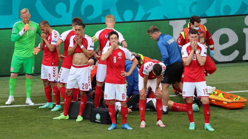 Denmark's players react as their teammate Christian Eriksen lays injured on the ground during...
