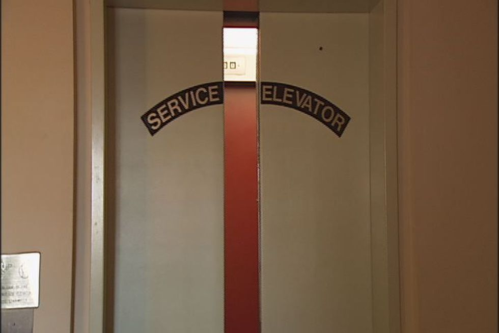 The doors slowly creak closed on the service elevator inside, where two people died.