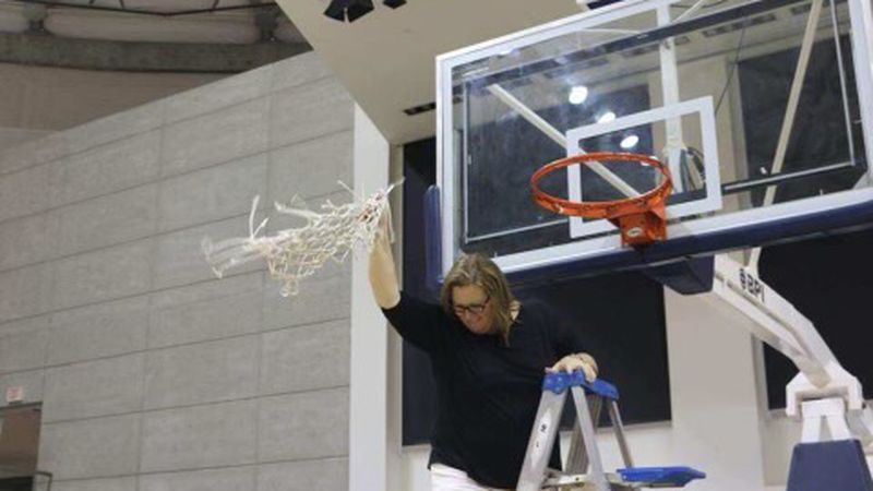 Coach Amy Strenth cutting down the net at Georgia Southwestern after the Panthers win a region...